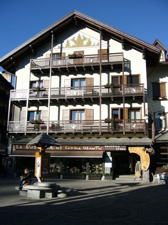 Drveni oglasni stup sa alpskim krovićem i kamena klupčica za sjedenje, u pozadini još jedna zgrada sa karakterističnim detaljima