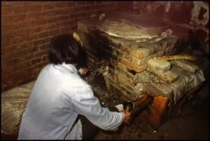 Jedna teta tada ponovno upali vatru na žaru dodajući lopaticom piljevinu u pećicu, a desno rukom upuhuje zrak pomoći mijeha (kao da pili drva)